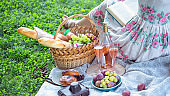 Summer - picnic in the meadow.  girl sitting reading a book and near a picnic basket and baguette, wine, glasses, grapes and rolls