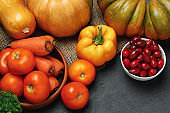 Assortment of vegetables including pumpkin, tomatoes and peppers on black background