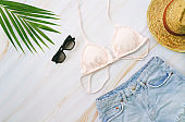 Flat lay of summer items with pastel bikini, sunglasses, jeans, hat and green tropical plant  on marble background, fashion and summer concept