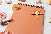 Brown open notepad surrounded by sea shells on white wooden table closeup