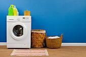 Washing machine with laundry on blue wall background
