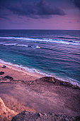 Sea surf waves on Bali beach Melasti pink purple sunset scenery with cliff view on sea horizon with dramatic sunset sky with surf waves as vertical tropical island background