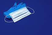 Medical gloves and surgical protective face mask on dark blue background