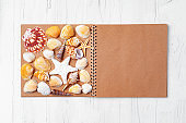 Open notepad with sea shells on white wooden background