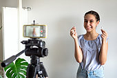Teen girl blogger influencer recording video blog concept speaking looking at smartphone on tripod at home. Teenager social media vlogger shooting vlog, streaming online podcast on mobile phone.