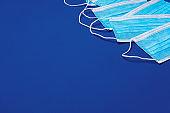 Medical face mask on blue background. Coronavirus prevention concept