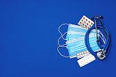 Medical face masks and stethoscope on blue background