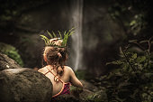 Lonely pensive child girl in wild forest looking at waterfall with plant wreath on her head as exploring wild nature concept