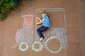 Cute toddler boy, playing with chalks, drawing on the pavement, riding train, lying on the ground