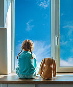 Little four years old girl sitting back on the windowsill with bunny soft toy looking outside