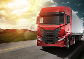 Red modern truck moving fast on the road at sunset with natural landscape
