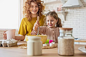 Mother and daughter prepare a cake together in the kitchen