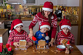 Children, boys, decorating home made ginger bread houses at home with mom helping