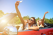 Young friends take a selfie in a cabriolet car