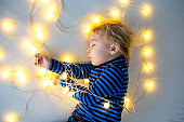 Little baby boy, sleeping with teddy bear in bed in heart made by lights