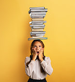 Young child student worried due to too much books to read and study. Yellow background