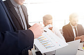 Team of business person works together on company statistics. Concept of teamwork