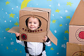 Sweet toddler boy, dressed as an astronaut, playing at home with cardboard rocket and handmade helmet