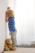 Child, toddler boy, punished in the corner for mischieves