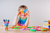 Happy little girl playing with colorful square shapes using it like eye glasses