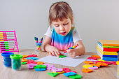 Beautiful little girl drawing with wax crayons and geometrical shapes