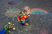 Cute toddler. playing in the rain with chalks, drawing on the asphalt, having fun