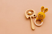 Wooden toys elephant beanbag and knitted bunny teether on beige background
