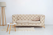 A beige sofa with a decorative pillow, a coffee table and a lamp in a spacious white living room. Spacious room interior with comfortable sofa against a white wall. Home decor. Scandinavian style