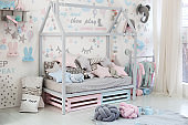 Empty cozy children's room with a white wall with stickers, toys, a bed with pillows. Scandinavian interior of a children's room. Wooden bed in the shape of house with toys and a blanket. Kindergarten