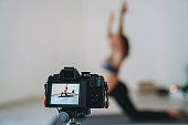 Yoga teacher is recording a pregnancy yoga lesson to upload it online