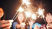 Group of young Asian college student friends lit light sparkler, sing and dance together at beach camping tent. Party people, love friendship relationship, or outdoor camping activity concept
