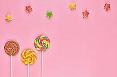 Sweet lollipop and candy on pink background
