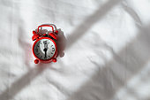 Red analog clock on white rumpled sheets. Top view, flat lay, copy space. Horizontal. Concept of awakening, sleep, early rise, productivity, productive day. For social media, blog. Minimal style
