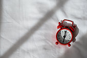Red analog clock on white rumpled sheets. Top view, flat lay, copy spase. Horizontal. Concept of awakening, sleep, early rise, productivity, productive day. For social media, blog. Minimal style