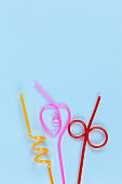 Disposable curly plastic multicolored tubules for drinks on pastel blue background, copy space. Festive concept, party, birthday. Flat lay, top view. Vertical. For social media