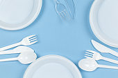 Disposable plastic dishes, plates, knives, forks on blue background. Frame of objects. Environmental pollution, rejection of non-recyclable plastic, Eco, zero waste concept