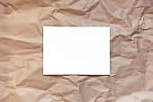 Crumpled craft brown paper background with white sheet in middle. Copy space. Horizontal. DIY, handicraft, back to school, ecology, plastic free concept, harvesting for mock up. Flat lay, top view