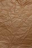 Abstract texture. Crumpled craft brown paper background. Copy space for text. Vertical. DIY, handicraft, back to school, ecology, plastic free concept, harvesting for mock up. Flat lay, top view