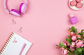 Modern female working space, top view. Women's or girls things, wireless headphones, roses, perfume, stationery on pink backround, copy space, flat lay. Work from home concept. For blog. Horizontal
