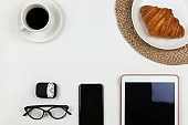 Modern working space of freelancer. Smartphone, coffee, tablet, croissant, glasses, headphones in case on white background, copy space, flat lay. Business breakfast, work from home, stay home concept