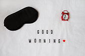Silk black sleep mask, inscription Good morning, red clock on white rumpled sheets. Top view, flat lay. Horizontal. Concept of rest, awakening, sleep. For social media, blog. Minimal style
