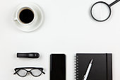 Modern unisex working space, top view. Notepad, pen, coffee, smart phone, magnifier, glasses on white background, copy space, flat lay. Desktop of freelancer. Work from home concept. Monochrome image
