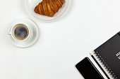 Modern working space of freelancer. Smart phone, coffee, notebook, pencil, croissant on white background, copy space, flat lay. Business breakfast, work from home concept