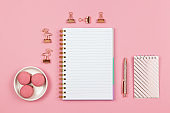 Modern female working space, top view. Notebooks, pen, clamps on pink backround, copy space, flat lay. Desktop of freelancer, student. Work from home, back to school, education concept. Horizontal