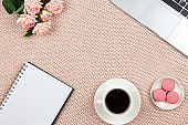 Work from home concept. Modern female working space, top view. Laptop, coffee, cakes, roses, notebook on knitted blanket, copy space, flat lay. Desktop of freelancer. Frame of objects. Horizontal