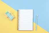 Notebook, pen, deck chair on two-color background yellow and blue, copy space, flat lay. Working space of freelancer, top view. Freelance, planning of vacation, travel concept. Horizontal