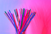 Disposable plastic multicolored tubules for drinks in glass on neon background, copy space. Festive concept, party, birthday. Flat lay, top view. Horizontal