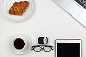 Business breakfast concept. Modern unisex working space, top view. Laptop, coffee, tablet, croissant, glasses, headphones in case on white background, copy space, flat lay. Desktop of freelancer