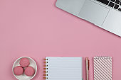 Modern female working space, top view. Laptop, notebooks, pen in rose gold color, macarons on pink background, copy space, flat lay. Desktop of blogger, freelancer. Work from home concept. Horizontal