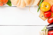 Assorted raw organic fresh vegetables on white wooden table. Fresh garden vegetarian food. Autumn seasonal image of farmer table with rye, pumpkin, cucumbers, tomatoes, eggplant and other